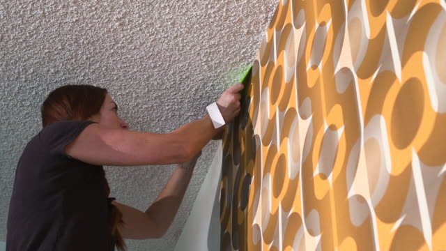 vídeos de stock e filmes b-roll de real woman improving, renovating and decorating her home by hanging 1970's retro wallpaper - papel de parede