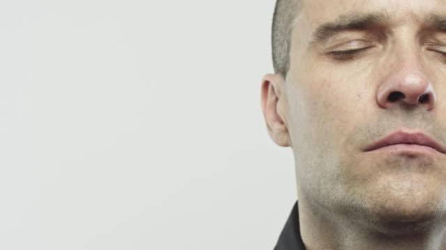 stockvideo's en b-roll-footage met echte jongeman met gesloten ogen - met de ogen dicht