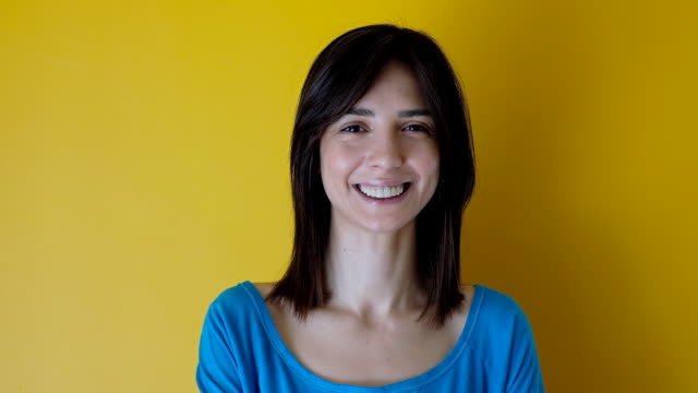 vídeos de stock e filmes b-roll de real young woman looking happy against yellow background - parte de uma série