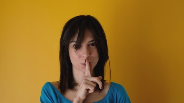 real young woman making silence gesture and looking at camera yellow background - silence stock videos & royalty-free footage