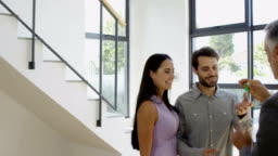 Real-estate agent giving keys to couple