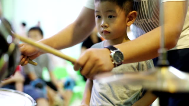 Realtime clip of Asian child learning drum kit