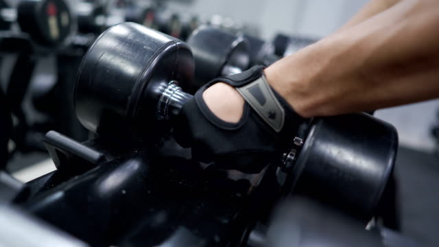 4k realtime hand picking up dumbbells to workout in gym - arm curl stock videos and b-roll footage