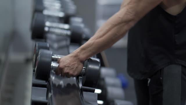 vídeos de stock e filmes b-roll de 4k realtime hand picking up dumbbells to workout in gym - flexão de braço com peso