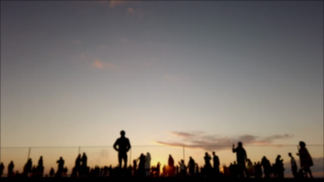 4k realtime . silhouette crowd at rooftop at sunset. - directly below stock videos & royalty-free footage