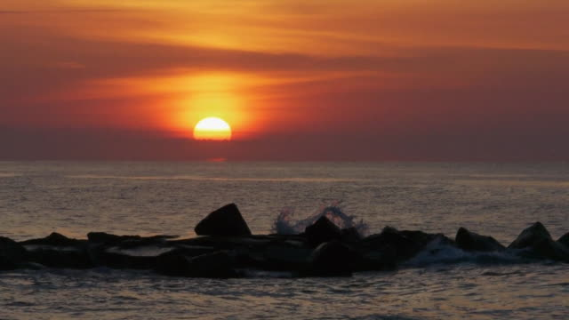 real-time telephoto shot of orange sun just above ocean horizon, behind clouds, avon-by-the-sea, new jersey, atlantic ocean - orange new jersey stock videos & royalty-free footage