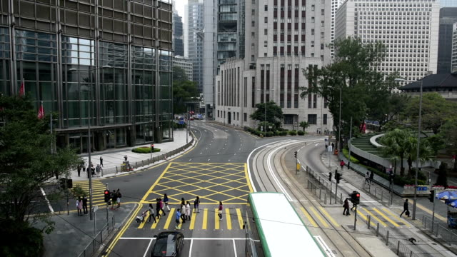 hd real-time video , cityscape of hong kong , a busy traffic intersection shuttle traffic - straßenbahnstrecke stock-videos und b-roll-filmmaterial