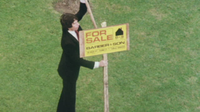 1980 montage realtor installing for sale sign on lawn, and suburban semi-detached housing development / united kingdom - home ownership stock videos & royalty-free footage