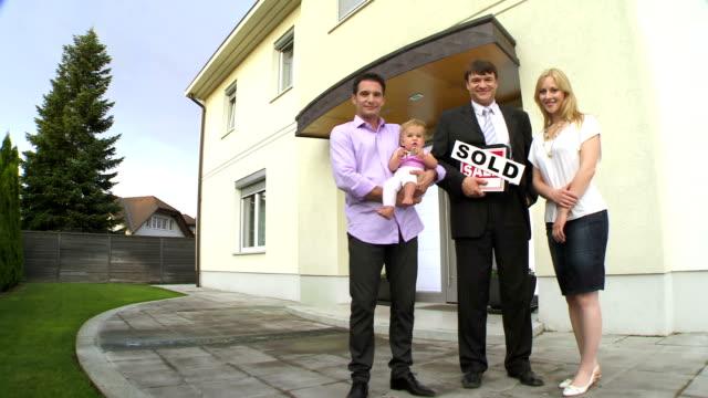 hd crane: makler posieren mit der familie - immobilienschild stock-videos und b-roll-filmmaterial