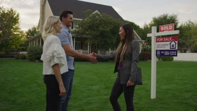 realtor shaking hands with proud couple on lawn of sold house / pleasant grove, utah, united states - sälja bildbanksvideor och videomaterial från bakom kulisserna
