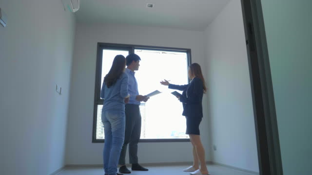 realtor showing an empty apartment for rent to a young married couple - 25 29 years stock videos & royalty-free footage