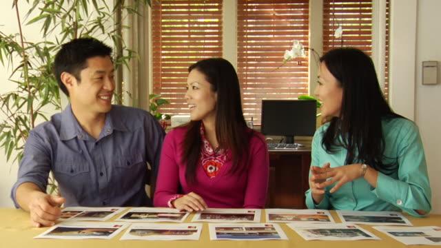 stockvideo's en b-roll-footage met ms zi realtor showing couple real estate flyers in home office / los angeles, california, usa - man met een groep vrouwen