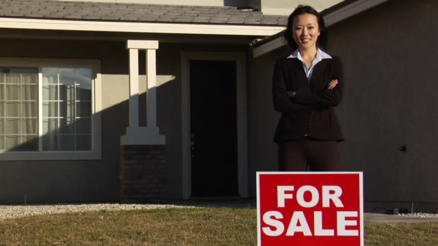 sm ws realtor standing in front of two-story house with for sale sign on lawn / los angeles, california, usa - in front of stock videos and b-roll footage