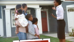 Realtor Stands Outdoors Showing Family Around House For Sale