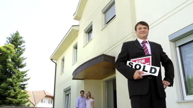 hd crane: makler mit happy new owners - immobilienschild stock-videos und b-roll-filmmaterial