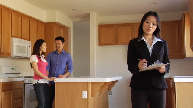 ms realtor writing on clipboard while couple looks around kitchen in new house / los angeles, california, usa - 男性と複数の女性点の映像素材/bロール