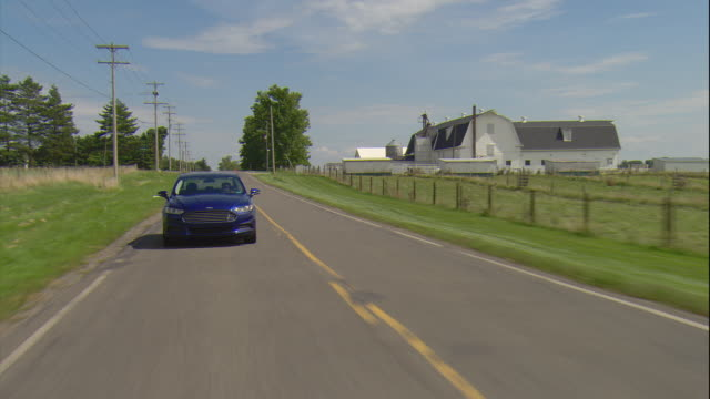 rear pov of a college student driving a blue sedan along a rural two lane road in east lansing, mi. - lansing stock videos and b-roll footage