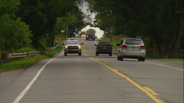 stockvideo's en b-roll-footage met rear pov of a white utility pickup truck driving on a rural two lane road in milford, mi. - commercieel landvoertuig