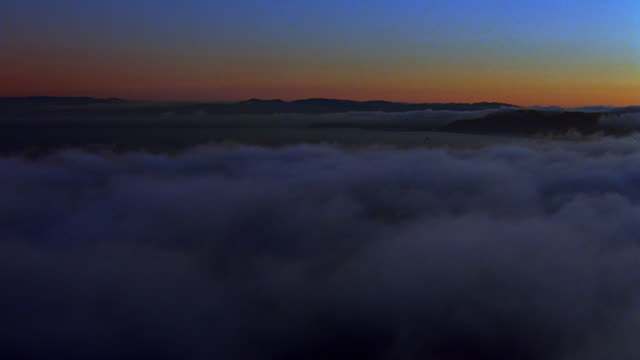 Rear aerial point of view over clouds covering coastline then over ocean at sunset / California