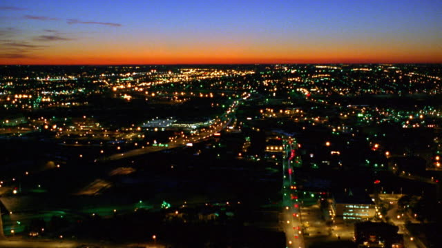 Rear aerial point of view over silhouetted downtown Kansas City with surrounding area in background at dusk / Missouri