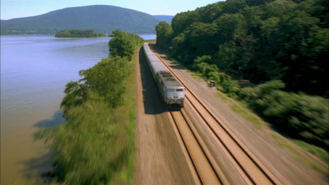 vídeos de stock, filmes e b-roll de rear aerial point of view over train traveling between hudson river and  forest / new york - trem de passageiros trem