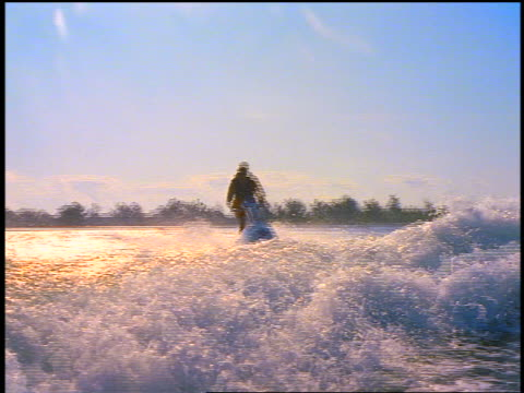 fast rear boat point of view pan man riding jet boat jumping over wake from boat - acquascooter video stock e b–roll
