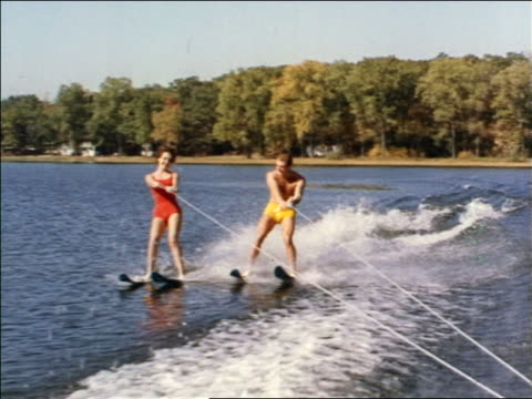 1962 rear boat point of view man + woman in swimsuits water skiing on lake / industrial - waterskiing stock videos & royalty-free footage