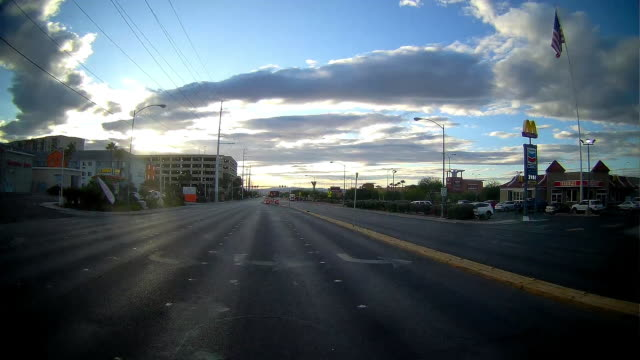 vídeos de stock e filmes b-roll de rear camera point of view of driving in las vegas with mcdonald's store in the background. - outdoor pursuit
