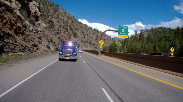 rear camera point of view of sunny day driving through colorado mountains - heavy goods vehicle stock videos & royalty-free footage