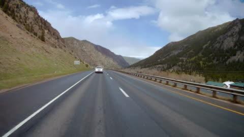 vídeos y material grabado en eventos de stock de rear camera point of view of sunny day driving through colorado mountains - sports utility vehicle