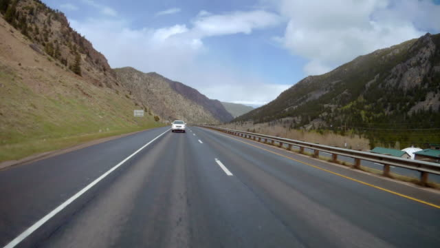 rear camera point of view of sunny day driving through colorado mountains - car stock videos & royalty-free footage