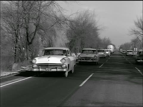 b/w 1957 rear car point of view of line of cars passing on country highway - 1957 stock videos & royalty-free footage