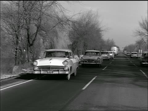 b/w 1957 rear car point of view of line of cars passing on country highway - 1957 bildbanksvideor och videomaterial från bakom kulisserna