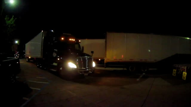 rear dashboard cam shot of a rest area parking lot on the interstate highway in america at night - autostrada interstatale americana video stock e b–roll