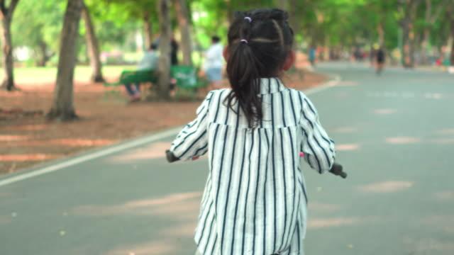 vidéos et rushes de vue suivante arrière : petite fille musulmane conduisant un vélo dans le stationnement public au coucher du soleil du week-end - roue