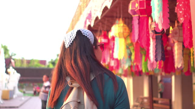 rear following view of southeast asian mid woman with winter cloth, hair cover, backpacker walking to looking at view of  home-made paper lamp,  religious symbol of local buddhism in thailand with feeling happiness, relaxation, enjoyment under sunlight. - religious symbol stock videos & royalty-free footage