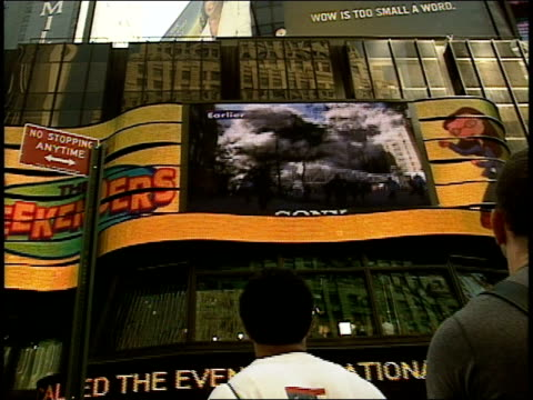 9/11/01 Rear front view of people in crowd look up at news headlines on zipper sign footage of people fleeing WTC on large video projection screen...