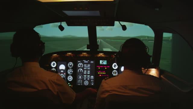 vídeos de stock, filmes e b-roll de ms rear internal view of pilots and instrument panel in professional flight simulator during landing, red r3d 4k - cabine de piloto de avião