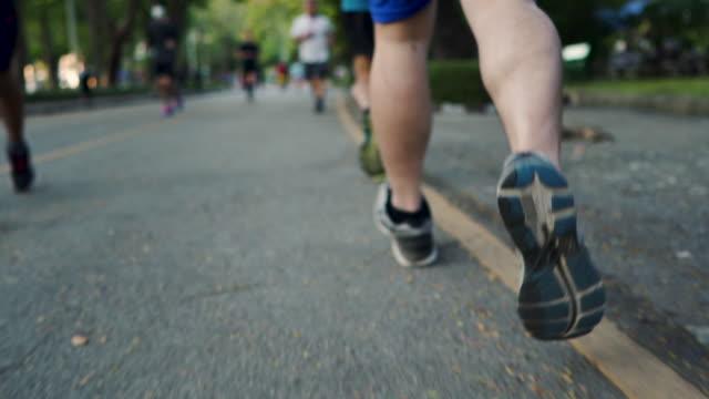 公共の公園でジョギングランナーのランニングシューズのリアローアングルローセクションビュー - 陸上選手点の映像素材/bロール