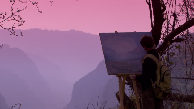 rear majed tawk, a young artist from the area, painting the pink hues of the sunset over a view of bsharri. - painting stock videos & royalty-free footage