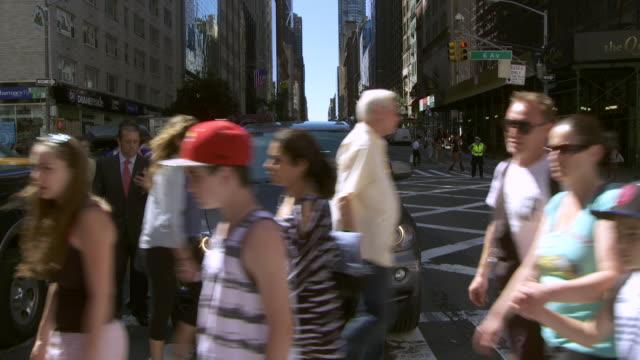 vídeos y material grabado en eventos de stock de rear point of view of people crossing the street at 34th st and 6th avenue in new york city - paso de cebra