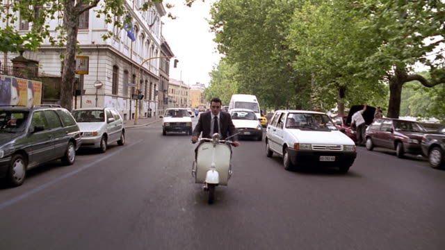 Rear point of view tracking shot businessman riding scooter in traffic on tree-lined city street / Rome, Italy