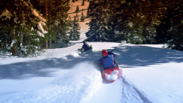 rear point of view two people snow kayaking down mountainside, past evergreen trees with 360 spin at end / aspen - winter sport stock videos & royalty-free footage