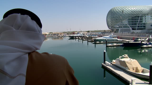 rear pointofview of an emirati man looking at yas island marina - dish dash stock videos & royalty-free footage