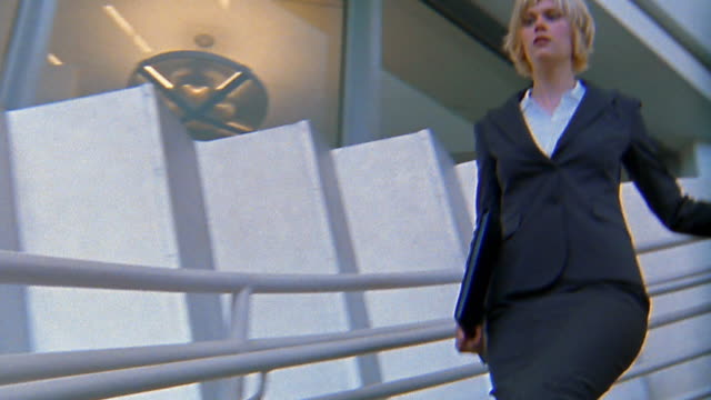 Rear running point of view businesswoman hurrying down stairs