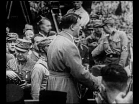 Rear shot Adolf Hitler speaks at event with Sturmabteilung guards facing him / Hitler addresses the Reichstag at the Kroll Opera House in 1933...