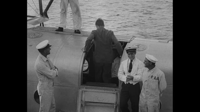 Rear shot aviator Charles Lindbergh walks up to doorway of seaplane American Clipper enters / mechanic stands by as propeller fires up for the...