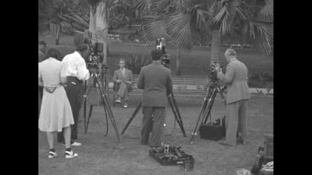 rear shot cameramen take film of edward duke of windsor and wallis simpson duchess of windsor as they sit on park bench in nassau the duke is now... - bahamas stock videos & royalty-free footage