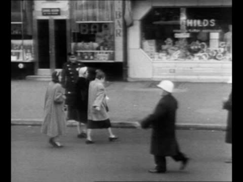 stockvideo's en b-roll-footage met rear shot civil defense worker gestures as he walks into street broadway theatre marquees in background detective story judy garland with bus parked... - rampenbestrijding