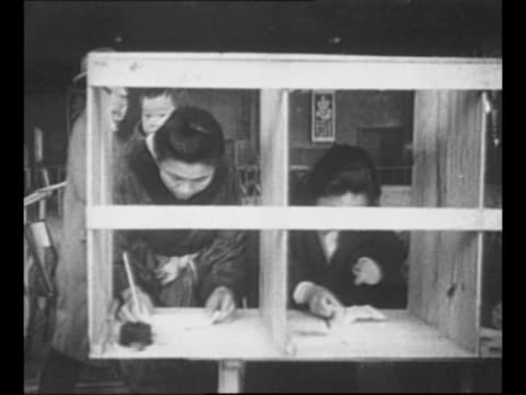 rear shot election workers hand ballots to approaching voters during first free japanese elections / montage men and women in voting booths one woman... - voting点の映像素材/bロール